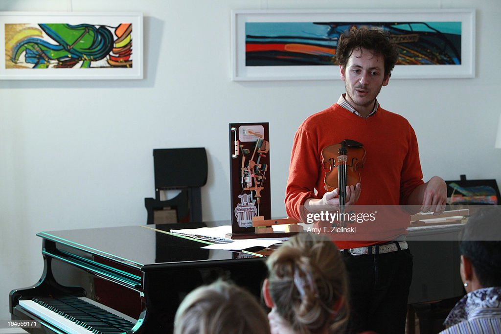 Piano tuner and technician Antoine Dubay holds a violin as he gives a workshop about the history of the piano and its mechanical parts near a Steinway grand piano in the Salon during 'It's All About Piano!' festival at The Institut Francais on March 24, 2013 in London, England. The festival is a collaboration from French Music Office to celebrate the piano with recitals from classical to jazz, film screenings, children's activities, workshops and cinema screenings exploring the musical instrument.