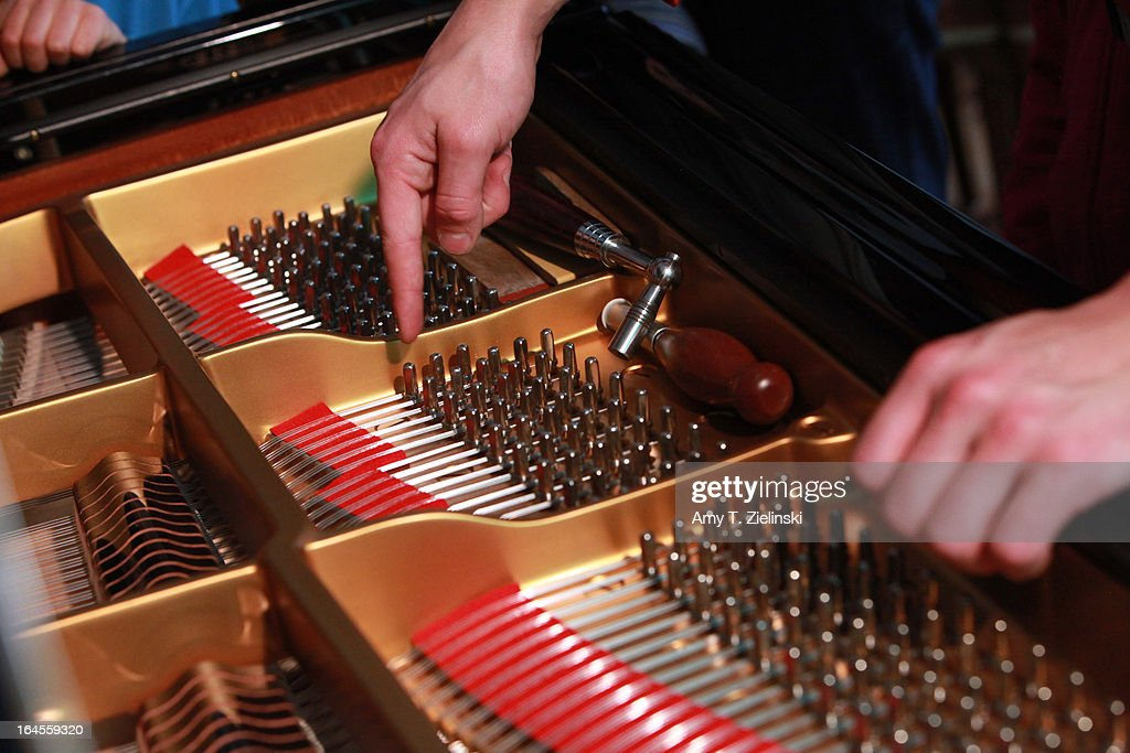 Piano tuner and technician Antoine Dubay points to the strings of a piano as he gives a workshop about the history of the piano and its mechanical parts near a Steinway grand piano in the Salon during 'It's All About Piano!' festival at The Institut Francais on March 24, 2013 in London, England. The festival is a collaboration from French Music Office to celebrate the piano with recitals from classical to jazz, film screenings, children's activities, workshops and cinema screenings exploring the musical instrument.