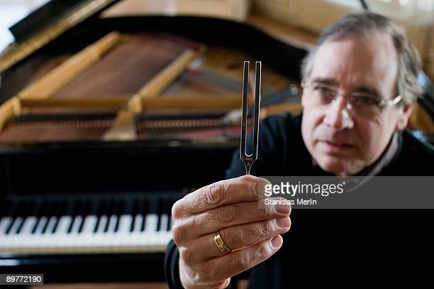 Piano tuner holding tuning fork