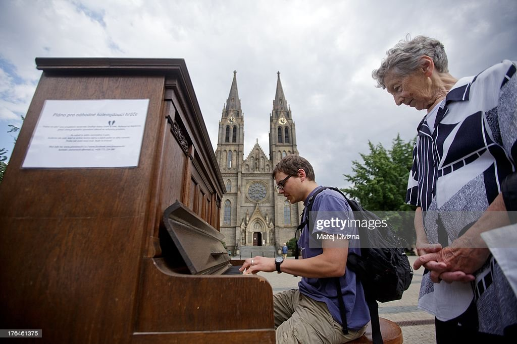 A piano tuner plays a piano during the first day of the 'Pianos on the street' project at Namesti Miru square on August 13, 2013 in Prague, Czech Republic. The project, by Prague cafe owner Ondrej Kobza, started in Prague today. Kobza placed pianos in five spots in the city centre for random passers-by to play. Similar projects run worldwide.