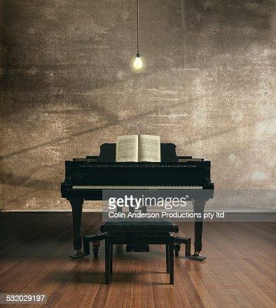 Piano under illuminated light bulb