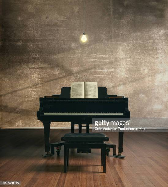 Piano under illuminated light bulb