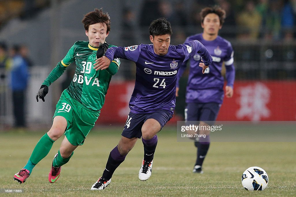 Piao Cheng (L) of Beijing Guo'an challenges Gakuto Notsuda of Hiroshima Sanfrecce during the AFC Champions League Group match between Hiroshima Sanfrecce and Beijing Guoan at Beijing Workers' Stadium on March 13, 2013 in Beijing, China.