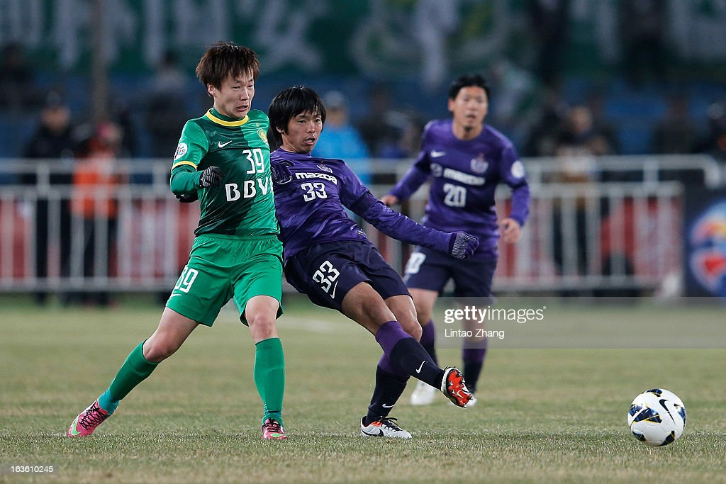 Piao Cheng (L) of Beijing Guoan challenges Tsukasa Shiotani of Hiroshima Sanfrecce during the AFC Champions League Group match between Hiroshima Sanfrecce and Beijing Guoan at Beijing Workers' Stadium on March 13, 2013 in Beijing, China.