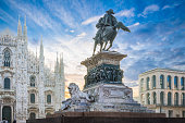 Square Duomo located in the center of Milan. Spectacular image of the monument to King Vittor Emmanuel II and of the cathedral of Milan in back light in the early morning