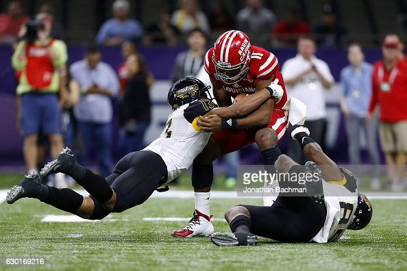 Picasso Nelson Jr #13 of the Southern Miss Golden Eagles and Ja'Boree Poole sack Anthony Jennings of the LouisianaLafayette Ragin Cajuns during the...