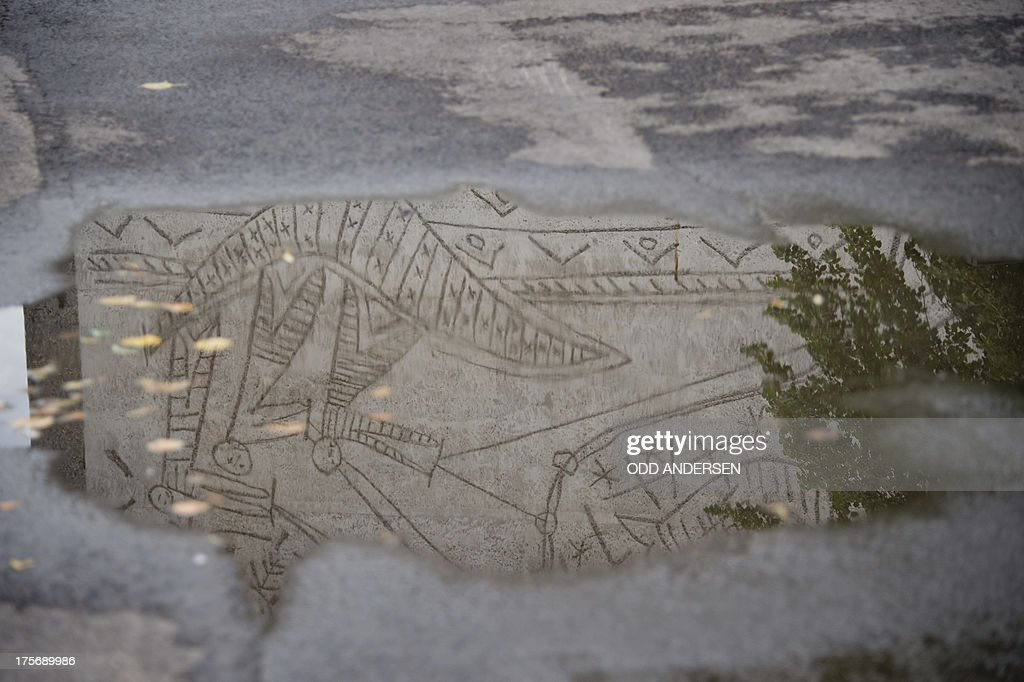 Picasso's mural art work 'The Fisherman' on the government quarter's 'Y building' reflects in a puddle in Oslo, Norway on August 6, 2013. The art work survived the 22nd July 2011 bombing unscathed, but other government buildings bearing the artist's murals were severely damaged. The Norwegian Directorate for Cultural Heritage fears that Picasso's first monumental concrete murals, which were made between the late 1950s and the early 1970s for two government buildings in Oslo, may be destroyed. The buildings were severely damaged during the deadly terrorist attack in the Norwegian capital in July 2011. The government is now considering whether to demolish the Modernist buildings that form the regjeringskvartal or government quarter.