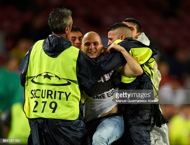 A pich invader is restrained by stewards during the UEFA Champions League group D match between FC Barcelona and Olympiakos Piraeus at Camp Nou on...