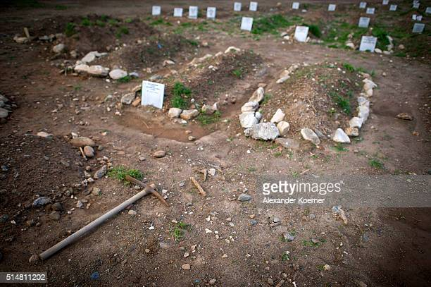 A pickaxe lies next to migrant graves who died during the attempt to reach the Island of Lesbos at a newly built cemetery on March 11 2016 in Kato...