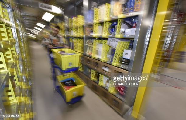 A 'picker' collects items from storage shelves to collates customers' orders at the Amazon electronic commerce company's logistics center in San...