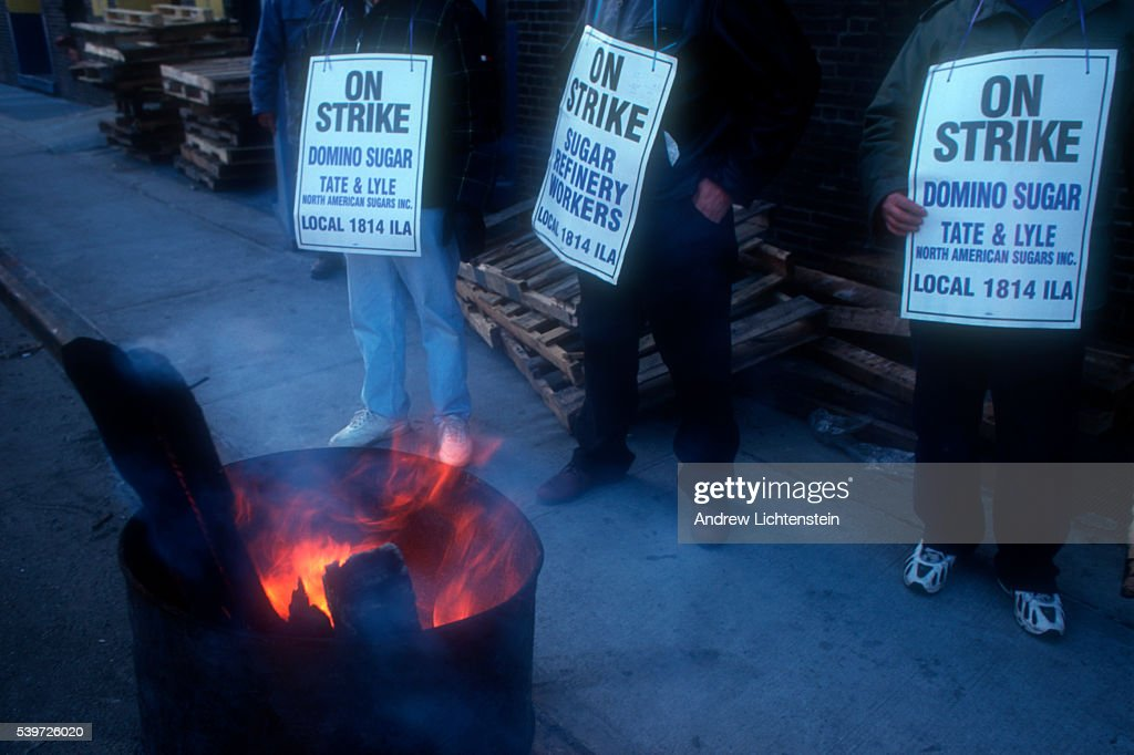 A picket line outside of Brooklyn's Domino sugar plant owned by Tate and Lyle where members of a longshoreman's local union are on strike try to stay...
