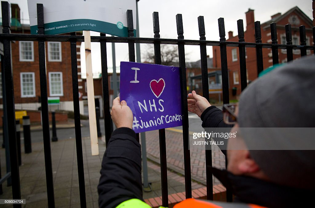 A picketer puts up a sign outside Maudsley Hospital during a 24-hour strike by junior doctors over pay and conditions in London on February 10, 2016. Thousands of junior doctors began a second strike at English hospitals on Wednesday against proposed new working conditions and pay rates. Junior doctors -- all medics below consultant level -- were providing emergency care only from 8:00am (0800 GMT) in the 24-hour strike. / AFP / JUSTIN TALLIS