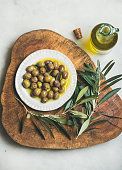 Pickled green Mediterranean olives and olive tree branch on wooden board and virgin olive oil in bottle over grey marble background, top view
