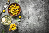 Pickled olives with olive oil. On a rustic background.