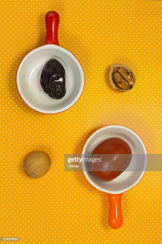 Pickled plums and tomatoes on a yellow background. Walnut. Still : Stock Photo