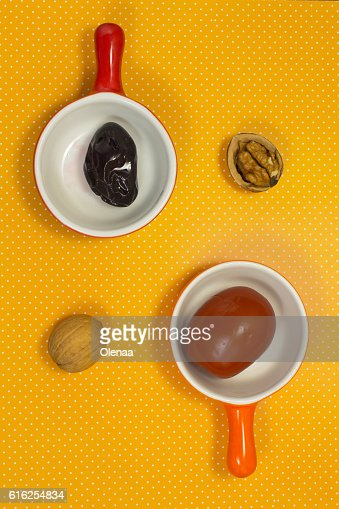 Pickled plums and tomatoes on a yellow background. Walnut. Still : Foto de stock