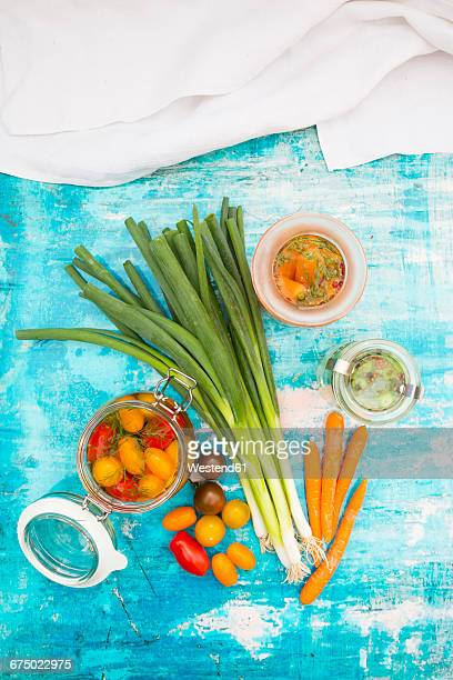 Pickled spring onions and tomatoes and fermented carrots in glasses