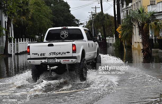 A pickup truck drives at a flooded street in downtown Charleston South Carolina on October 4 2015 Relentless rain left large areas of the US...