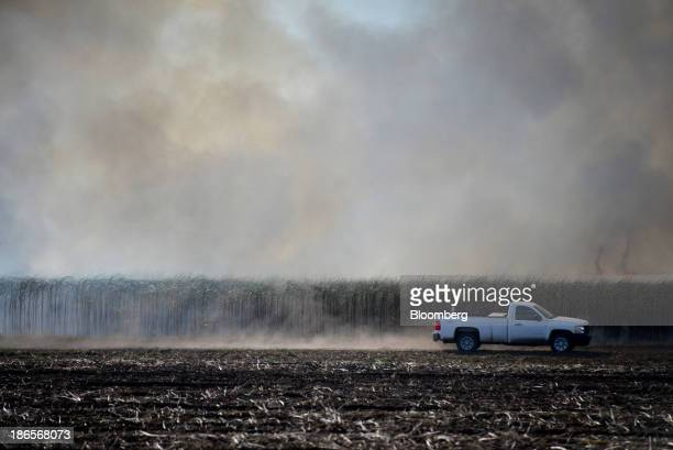 A pickup truck drives by as underbrush burns away during sugarcane harvest at a US Sugar Corp field in Belle Glade Florida US on Thursday Oct 31 2013...