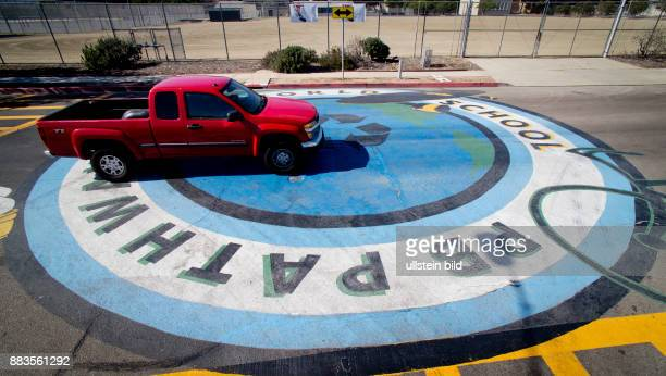 Pickup truck driving over a huge mural close to a school in Pacific Beach with a 'recycle' symbol in the center of it