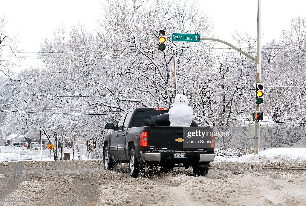 A pickup truck with a snowman in the back drives through the snow after the area is hit by a snowstorm on February 26, 2013 in Kansas City, Missouri. This is the second major snowstorm the midwest has seen this week dropping a half-foot or more of snow across Missouri and Kansas and cutting power to thousands...