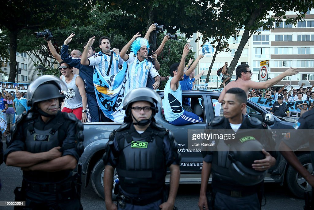 A pickup truck with Argentine football fans drive past riot police trying to control the fans and keep them from impeding vehicle traffic as they show their enthusiasm for their team playing in the FIFA World Cup on June 14, 2014 in Rio de Janeiro, Brazil. The Argentine team plays their first match tomorrow against Bosnia and Herzegovina.