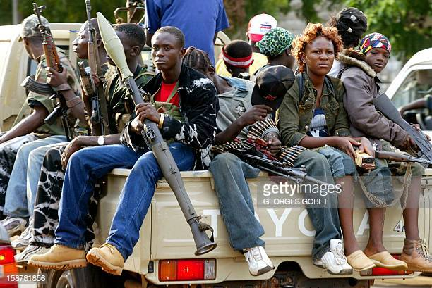 A pickup with young soldiers loyal to Liberian President Charles Taylor escorts Taylor's armoured SUV on a tour of the Monrovia defense line 29 June...