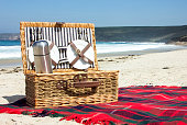 Landscape colour photo of a traditional wicker picnic basket on a tartan rug laid out on a sandy beach