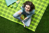 Smiling woman having a relaxing lunch break outdoors, she is sitting on the grass and eating a salad bowl