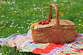 Spring picnic , Picnic basket and blanket on green grass in park, nature.