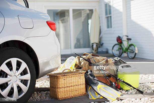 Picnic basket, fishing rod, flippers and bags outside car in driveway