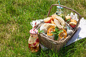 Picnic basket with food on green sunny lawn. Healthy eating.