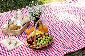 picnic bread croissant basket with fruit on  red white cloth and vase flower with jar of orange juice