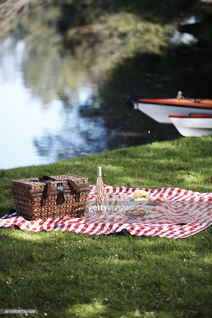 Picnic hamper and rug by lake, Seattle, Washington, USA : Stock Photo