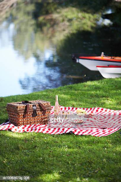 Picnic hamper and rug by lake, Seattle, Washington, USA