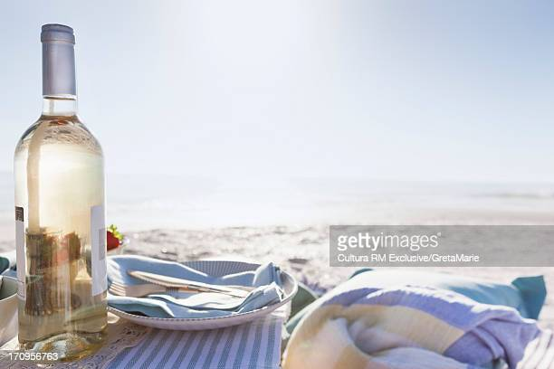 Picnic on beach with bottle of white wine
