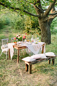 picnic, summer, holiday concept - festive table setting among large trees, openwork tablecloth, wood bench, chairs, colorful bouquet, jug of lemonade, fruit plates, candlesticks, selective focus