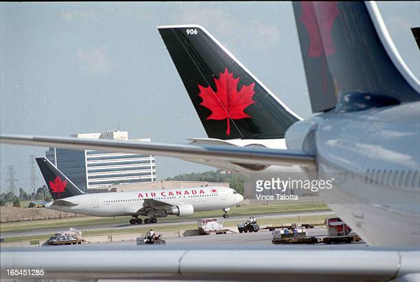 Pics of travellers in line at Air Canada deaparture areatravellers and people looking at departure board with Air Canada and travellers in line in...
