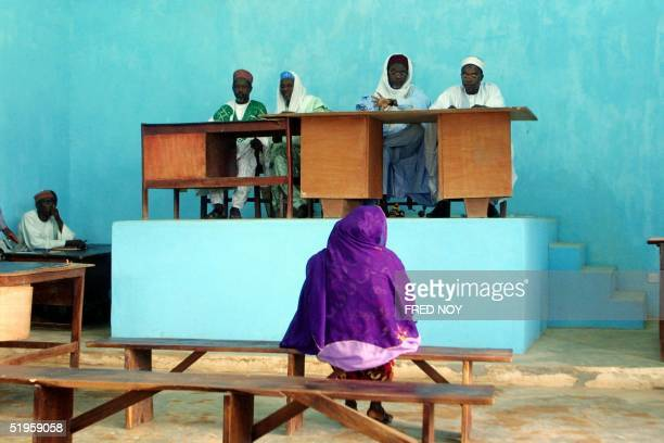 picture dated 08 July 2002 shows divorcee Amina Lawal sitting on a bench facing judges of the Sharia Islamic court The Funtua Upper Sharia court will...