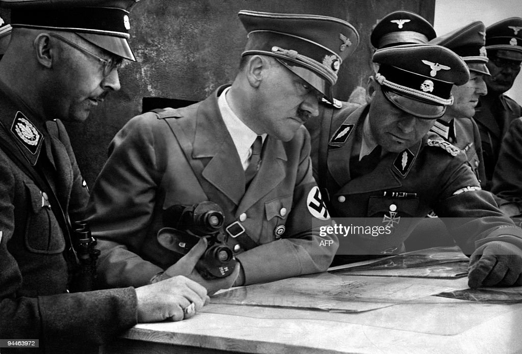A picture dated 1939 shows German Nazi Chancellor and dictator Adolf Hitler consulting a geographical survey map with his general staff including...