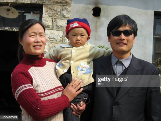 A picture dated March 28 2005 shows blind activist Chen Guangcheng with his wife and son Chen Kerui outside the home in Dondshigu village northeast...