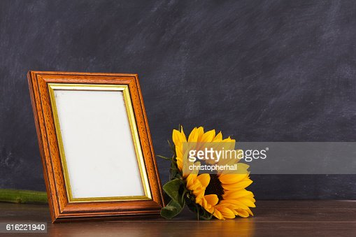 Picture frame and sunflower against a dirty blackboard backgroun : Photo
