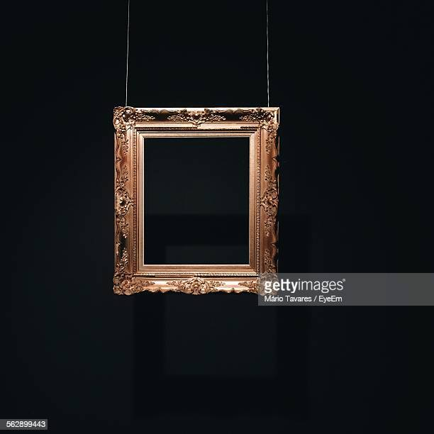 Picture Frame Hanging Against Black Background