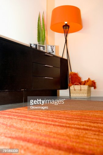 Picture frame on a cabinet with a floor lamp near it : Foto de stock