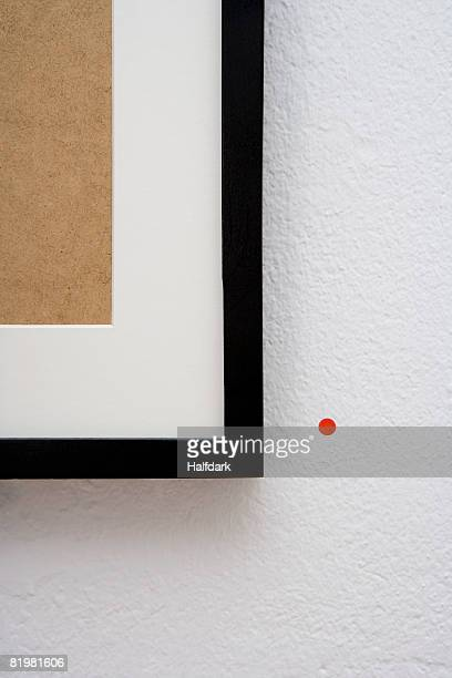 A picture frame with a red sticker next to it