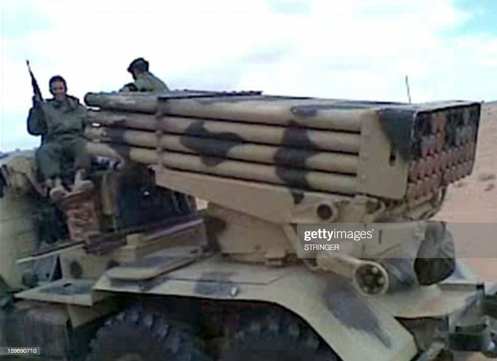 A picture grabbed on images obtained by AFP in Mali on January 18, 2013 and filmed with a mobile phone in 2012 shows fighters sitting on a truck carrying a missile launcher part of a rebel convoy in the Malian desert . BM-21 Grad multiple rocket launchers (on picture), the type of equipment that was once part of the Libyan army's arsenal, make up part of the convoy as do Mali army vehicles. The Malian army backed by French troops wrested a key central town from Islamist rebels, as the UN warned up to a million people could be driven from their homes by fighting in coming months. As a dramatic hostage siege unfolded in neighbouring Algeria -- where Islamists took hundreds captive in a gas field to retaliate for the week-old military intervention in Mali, sparking a deadly commando raid -- fighting has continued unabated on the ground in Mali. AFP PHOTO / STRINGER