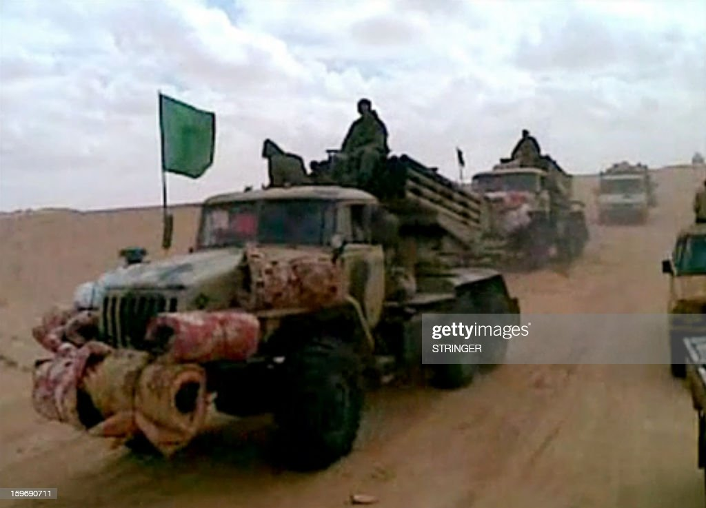 A picture grabbed on images obtained by AFP in Mali on January 18, 2013 and filmed with a mobile phone in 2012 shows fighters sitting on a truck with a Green flag part of a rebel convoy in the Malian desert . BM-21 Grad rocket launchers, the type of equipment that was once part of the Libyan army's arsenal, make up part of the convoy as do Mali army vehicles. The Malian army backed by French troops wrested a key central town from Islamist rebels, as the UN warned up to a million people could be driven from their homes by fighting in coming months. As a dramatic hostage siege unfolded in neighbouring Algeria -- where Islamists took hundreds captive in a gas field to retaliate for the week-old military intervention in Mali, sparking a deadly commando raid -- fighting has continued unabated on the ground in Mali. AFP PHOTO / STRINGER