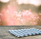 Empty tablecloth on wooden table and pink field  background.