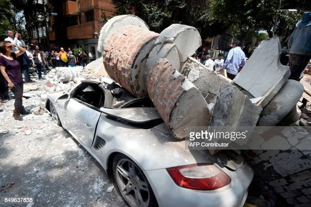 TOPSHOT Picture of a car crushed by debris from a damaged building after a quake rattled Mexico City on September 19 2017 A powerful earthquake shook...
