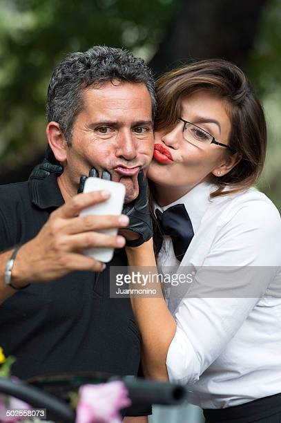 picture of a couple taking a self picture with his phone
